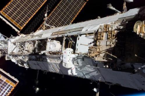 Un astronaute installe un instrument sur la poutre principale... (image NASA)